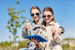 Τα ευτυχή κορίτσια με την παρουσίαση PC ταμπλετών φυλλομετρούν επάνω Στοκ φωτογραφία με δικαίωμα ελεύθερης χρήσης