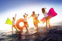 Τα ευτυχή κορίτσια που περπατούν στο ηλιοβασίλεμα ποτίζουν με τα κολυμπώντας στρώματα στοκ φωτογραφία
