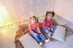 Τα ευτυχή μικρά κορίτσια χρησιμοποιούν smartphones για την ψυχαγωγία και κάθονται επάνω Στοκ Φωτογραφία