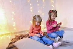 Τα ευτυχή μικρά κορίτσια χρησιμοποιούν smartphones για την ψυχαγωγία και κάθονται επάνω Στοκ Εικόνες