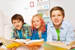 Τα ευτυχή νέα teens που διαβάζονται τα βιβλία και το χαμόγελο Στοκ Φωτογραφίες