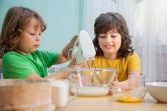 Τα ευτυχή οικογενειακά αστεία παιδιά προετοιμάζουν τη ζύμη, Στοκ Φωτογραφία