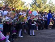 Τα ευτυχή παιδιά εγγράφτηκαν στη πρώτη θέση με τα δώρα στα χέρια τους στη σχολική ` s σοβαρή γραμμή στην ημέρα της γνώσης Στοκ Φωτογραφία
