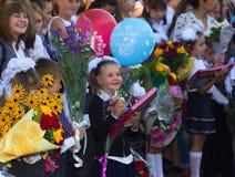 Τα ευτυχή παιδιά εγγράφτηκαν στη πρώτη θέση με τα δώρα στα χέρια των δασκάλων και των σπουδαστών γυμνασίου στη σχολική γραμμή Στοκ εικόνες με δικαίωμα ελεύθερης χρήσης