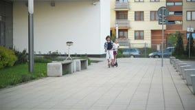 Τα ευτυχή παιδιά οδηγούν στο μηχανικό δίκυκλο λακτίσματος υπαίθριο Έχουν πολλή διασκέδαση που παίζει από κοινού φιλμ μικρού μήκους