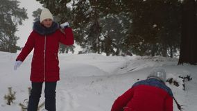 Τα ευτυχή παιδιά παίζουν τις χιονιές στο χιονώδες άσπρο βουνό στο πάρκο πεύκων Τα κορίτσια εφήβων παίζουν με το χιόνι στο χειμερι απόθεμα βίντεο