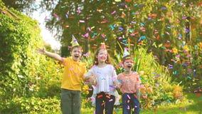Τα ευτυχή παιδιά στο κόμμα καρναβαλιού κάτω από το πετώντας κομφετί το καλοκαίρι σταθμεύουν απόθεμα βίντεο