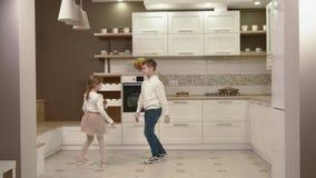 Τα ευτυχή παιδιά χορεύουν στην κουζίνα απόθεμα βίντεο