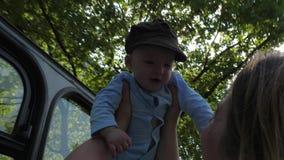Τα ευτυχή παιχνίδια γονέων με το γιο παραδίδουν επάνω backlight στα πράσινα δέντρα υποβάθρου στην κίνηση απόθεμα βίντεο