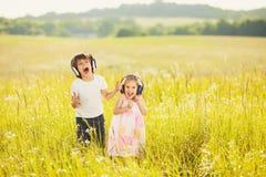 Τα ευτυχή παιδιά ακούνε μουσική στα ακουστικά Στοκ Εικόνα