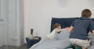 Τα ευτυχή παιδιά πηδούν στο κρεβάτι γονέων στη μητέρα και τον πατέρα το πρωί, εύθυμη οικογένεια στην κρεβατοκάμαρα φιλμ μικρού μήκους