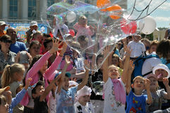 Τα ευτυχή παιδιά πιάνουν τις φυσαλίδες σαπουνιών στην οδό στην πόλη του Τ Στοκ Εικόνες