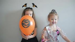 Τα ευτυχή χαμογελώντας κορίτσια έντυσαν στα κοστούμια αποκριών κρατώντας τα μπαλόνια και την τοποθέτηση αέρα φιλμ μικρού μήκους