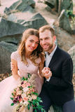 Τα ευτυχή newlyweds κοιτάζουν σε έναν φωτογράφο Ο άνδρας και η γυναίκα στα εορταστικά ενδύματα κάθονται στις πέτρες κοντά στη γαμ Στοκ εικόνες με δικαίωμα ελεύθερης χρήσης