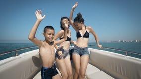 Τα ευτυχή teens έχουν το χρόνο των ζωών τους χορεύοντας σε μια βάρκα απόθεμα βίντεο
