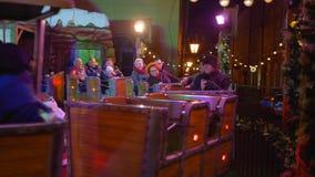 Τα ευτυχείς παιδιά και οι ενήλικοι οδηγούν το μυθικό τραίνο σε έναν κύκλο κατά τη διάρκεια των διακοπών Χριστουγέννων απόθεμα βίντεο