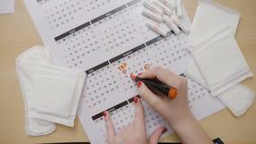 Τα εφηβικά χέρια με το κόκκινο καρφί γυαλίζουν τον έλεγχο του ημερολογίου και τον προγραμματισμό πόσου tampons θα χρειαστεί για τ φιλμ μικρού μήκους
