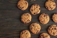 Τα εύγευστα μπισκότα τσιπ σοκολάτας στο ξύλινο υπόβαθρο, επίπεδο βάζουν στοκ εικόνα με δικαίωμα ελεύθερης χρήσης