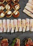 Τα εύγευστα πρόχειρα φαγητά από τα μικρά σάντουιτς με το ζαμπόν και τα πράσινα, χύνουν Στοκ Εικόνες