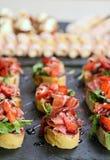 Τα εύγευστα πρόχειρα φαγητά από τα μικρά σάντουιτς με το ζαμπόν και τα πράσινα, χύνουν Στοκ Φωτογραφία