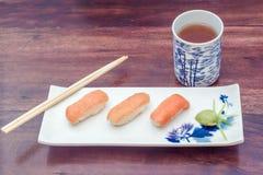 τα εύγευστα σούσια εξυπηρέτησαν τον ξύλινο πίνακα με το τσάι Στοκ φωτογραφίες με δικαίωμα ελεύθερης χρήσης