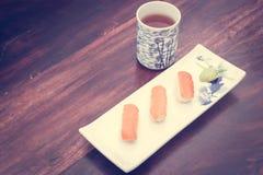 τα εύγευστα σούσια εξυπηρέτησαν τον ξύλινο πίνακα με το τσάι Στοκ Εικόνες