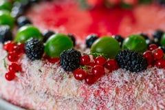 Τα εύγευστα υγιή χορτοφάγα τρόφιμα, δεν ψήνουν cheesecake φραουλών, που διακοσμείται με τα φρέσκα κόκκινα μούρα και την πράσινη μ Στοκ Φωτογραφία