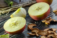 Τα εύγευστες φρέσκες κόκκινες μήλα και οι φέτες του ξηρού μήλου είναι στοκ εικόνες