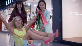 Τα εύθυμα κορίτσια shopaholics που έχουν τη διασκέδαση αγοράζουν επάνω τα καροτσάκια με τα μέρη των τσαντών αγορών ενώ αγορές στη απόθεμα βίντεο
