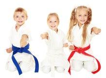 Τα εύθυμα μικρά παιδιά στο κιμονό κάθονται εθιμοτυπικό karate θέτουν και χτυπούν έναν βραχίονα που μονώνεται Στοκ Εικόνες