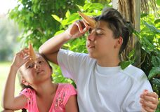 Τα εύθυμα παιδιά έχουν τη διασκέδαση τρώγοντας τα παγωτά Στοκ Φωτογραφίες