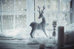 Τα ελάφια λογαριάζουν τη στάση στο παράθυρο στο υπόβαθρο του ντεκόρ Χριστουγέννων Αναμονή ένα θαύμα Στοκ Εικόνες