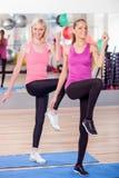 Τα ελκυστικά λεπτά κορίτσια κάνουν τις ασκήσεις στη γυμναστική Στοκ Εικόνες