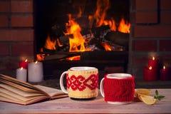 Τα ζεστά ποτά στις κούπες, το βιβλίο και τα κεριά στον ξύλινο πίνακα εκτός από άνετο ανοίγουν πυρ τη θέση Έννοια διακοπών φθινοπώ στοκ φωτογραφίες με δικαίωμα ελεύθερης χρήσης
