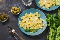 Τα ζυμαρικά ψεκάζονται με το τυρί που εξυπηρετείται στα μπλε πιάτα με το arugula, τις ελιές και τις παστωμένες κάπαρες Στοκ εικόνα με δικαίωμα ελεύθερης χρήσης