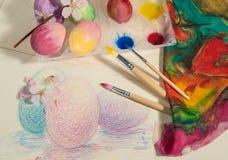 Τα ζωγραφισμένα στο χέρι αυγά Πάσχας με τις βούρτσες ζωγράφων, ζωηρόχρωμο ύφασμα, watercolors και άνθος αμυγδάλων, τακτοποίησαν σ Στοκ Φωτογραφία