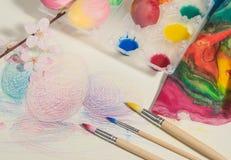 Τα ζωγραφισμένα στο χέρι αυγά Πάσχας με τις βούρτσες ζωγράφων, ζωηρόχρωμο ύφασμα, watercolors και άνθος αμυγδάλων, τακτοποίησαν σ Στοκ Εικόνες