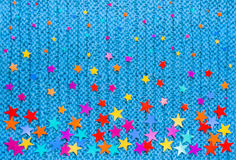 Τα ζωηρόχρωμα αστέρια των διαφορετικών μεγεθών σε ένα μπλε πλέκουν το υπόβαθρο στοκ φωτογραφία με δικαίωμα ελεύθερης χρήσης