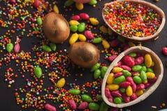 Τα ζωηρόχρωμα αυγά Πάσχας και ψεκάζουν στο μαύρο υπόβαθρο Στοκ Φωτογραφίες