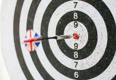 Τα ζωηρόχρωμα βέλη επιβιβάζονται κοντά επάνω με τα βέλη στο bullseye σημαία Στοκ Φωτογραφία