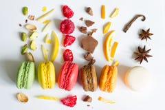 Τα ζωηρόχρωμα γαλλικά macarons αφαιρούν ακόμα τη ζωή με τα φρούτα και τα συστατικά στο άσπρο υπόβαθρο Στοκ εικόνες με δικαίωμα ελεύθερης χρήσης