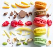 Τα ζωηρόχρωμα γαλλικά macarons αφαιρούν ακόμα τη ζωή με τα φρούτα και τα συστατικά στο άσπρο υπόβαθρο Στοκ φωτογραφία με δικαίωμα ελεύθερης χρήσης