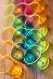 Τα ζωηρόχρωμα διαφανή φλυτζάνια ευθυγράμμισαν το ένα δίπλα στο άλλο για τα ποτά κομμάτων Στοκ Εικόνα
