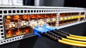 Τα ζωηρόχρωμα καλώδια οπτικής ίνας υψηλής ταχύτητας σύνδεσαν με το διακόπτη εξοπλισμού κεντρικών υπολογιστών δικτύων σύννεφων μέσ στοκ εικόνα