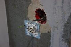 Τα ζωηρόχρωμα καλώδια που κολλούν από τον τοίχο, επισκευάζουν το διαμέρισμα, το σπίτι ή το γραφείο ηλεκτρική καλωδίωση η λάμπα φω στοκ εικόνες