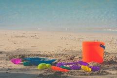 Τα ζωηρόχρωμα παιχνίδια παραλιών ή τα παιχνίδια παιδιών στην παραλία άμμου με seascape βλέπουν στο υπόβαθρο Στοκ Εικόνα