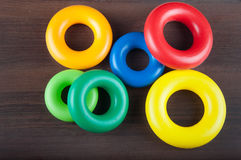 Τα ζωηρόχρωμα πλαστικά δαχτυλίδια βάζουν στο ξύλινο υπόβαθρο Στοκ εικόνες με δικαίωμα ελεύθερης χρήσης