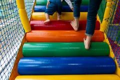 Τα ζωηρόχρωμα σκαλοπάτια στα παιδιά παίζουν το σπίτι, με τα πόδια παιδιών αναρριμένος επάνω στην κινηματογράφηση σε πρώτο πλάνο Στοκ Φωτογραφία