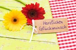 Τα ζωηρόχρωμες λουλούδια και η ευχετήρια κάρτα με το γερμανικό κείμενο, Herzlichen Glueckwunsch, σημαίνουν τα συγχαρητήρια στοκ φωτογραφίες με δικαίωμα ελεύθερης χρήσης