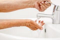 Τα ηλικιωμένα πλυσίματα γυναικών παραδίδουν το λουτρό στοκ φωτογραφία με δικαίωμα ελεύθερης χρήσης